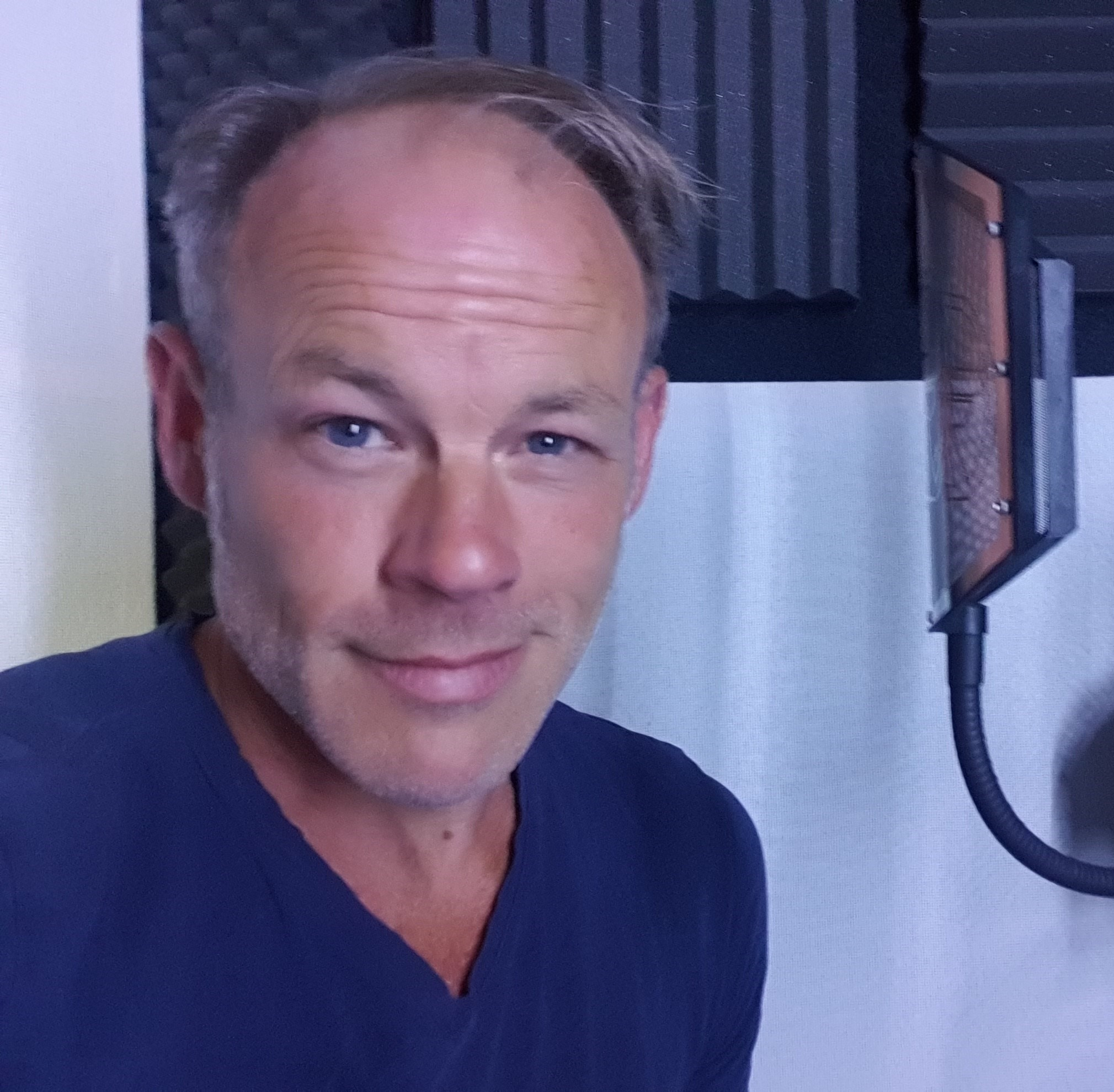 Photograph of male English voiceover artist Anthony Hewson in the recording booth