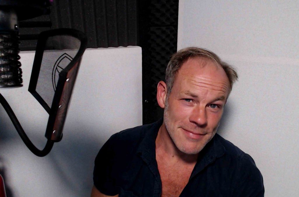 English voice actor Anthony Hewson in his recording booth - head and shoulders photograph with microphone and pop filter just in shot